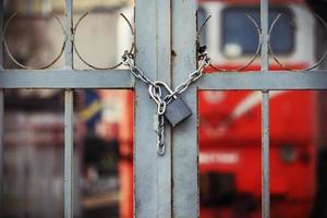 Locked padlock hanging on chain on closed gate to railway photo