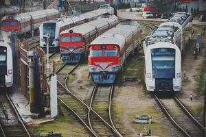 Various red and blue trains standing on rails photo