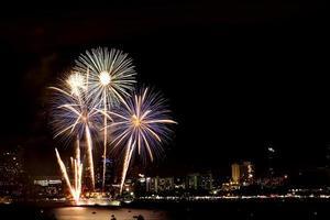 muchos fuegos artificiales destellantes con fondo de paisaje nocturno celebran el año nuevo. foto