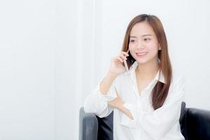 Young asian woman talking on smart phone on the chair. photo