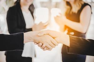 Business people shaking hands after finish reach agreement for startup new project. Negotiating and Happy working concept. Handshake gesturing connection deal concept. People and teamwork theme photo