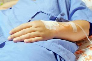 Goteo intravenoso de solución salina en una mano paciente mujer foto