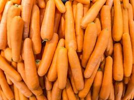 Organic carrot. Texture background of fresh large orange carrots, carrots are good for health, healthy ripe carrot for preparing meal photo
