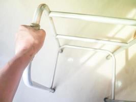 la mano izquierda agarra las ayudas para caminar, equipo médico para pacientes que no pueden caminar foto