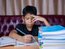 niño haciendo los deberes y leyendo en una mesa de madera con una pila de libros al lado del fondo es un sofá rojo y cortinas color crema. foto