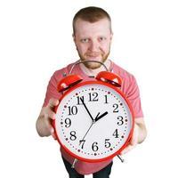 hombre barbudo sosteniendo un despertador rojo foto