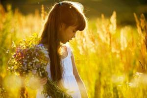 niña con un ramo de flores silvestres foto