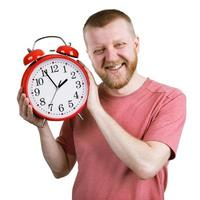 hombre barbudo con un despertador rojo foto