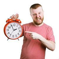 hombre descontento sosteniendo un gran reloj de alarma foto