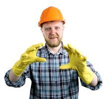 hombre en un casco y guantes de goma amarillos foto