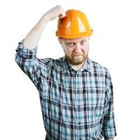 El hombre golpea su mano en el casco protector foto
