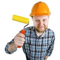 Trabajador de la construcción en un casco con un rodillo de pintura foto