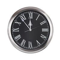el reloj de la oficina muestra cinco minutos para las doce foto