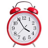 El despertador rojo muestra cinco minutos para las cuatro. foto