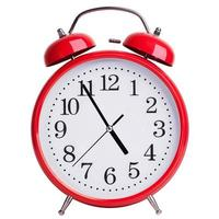 reloj despertador redondo que muestra casi cinco foto