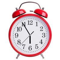 El despertador rojo muestra cinco minutos para las seis. foto