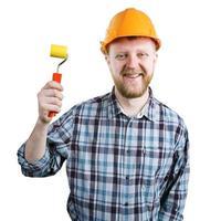 hombre en un casco con un rodillo de pintura foto