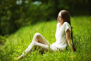 Pensive woman sitting on the grass photo