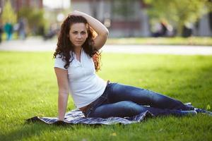 hermosa mujer en jeans se sienta en la hierba foto