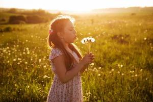 Girl blowing a bouquet of dandelions photo