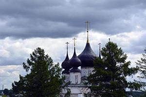 cúpulas de la iglesia con cruces contra el cielo azul. templo de piedra blanca entre los árboles. foto