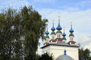 cúpulas de la iglesia con cruces contra el cielo azul. templo de piedra blanca en el pueblo ruso. foto