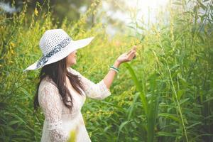 Beauty Asian woman in white dress and wing hat walking in rapeseed flower field background. Relaxation and travel concept. Wellness happy life of girl on vacation. Nature and people lifestyle photo