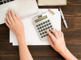 Manos de mujer en la calculadora y portátil, bolígrafo, tarjeta de memoria USB y otros elementos sobre fondo de madera oscura. concepto de negocio. contabilidad financiera. vista superior. foto