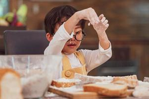 Portrait cute little Asian happiness boy interested in baking bakery with funny in home kitchen. People lifestyles and Family. Homemade food and ingredients concept. Baking Christmas cake and cookies photo
