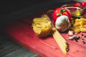 Tasty appetizing italian spaghetti pasta ingredients for kitchen cuisine with tomato, cheese parmesan, olive oil, fettuccine and basil on wooden brown table. Food Italian recipe homemade. Top view photo