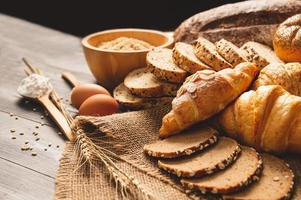 Different kinds of bread with nutrition whole grains on wooden background. Food and bakery in kitchen concept. Delicious breakfast gouemet and meal. Carbohydrate organic food cuisine homemade photo