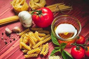 Sabrosos y apetitosos ingredientes de pasta de espagueti italianos para la cocina de la cocina con tomate, queso parmesano, aceite de oliva, fettuccine y albahaca en la mesa de madera marrón. comida italiana receta casera. vista superior foto