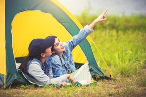 Two close friend Asian friendship relax in camping tent in green meadow on lake side view background. Girl pointing finger to sky. People lifestyle travel on vacation concept. Summer picnic activity photo