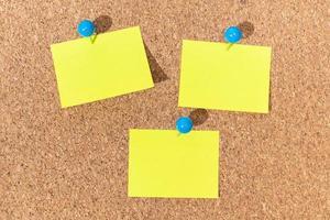 grupo de notas adhesivas amarillas en un tablero de corcho para agregar texto. maqueta de plantilla foto