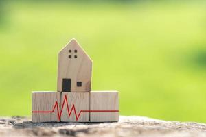 The concept of a crisis situation time financial difficulty is represented by a wooden cube with a house model and a heart pulse. photo