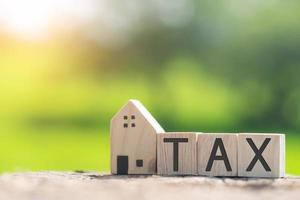 On a wooden cube background, the word tax appears. The concept of a business financial loan. photo