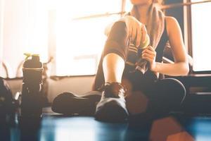 deporte mujer sentada y descansando después de entrenar o hacer ejercicio en el gimnasio con batido de proteínas o agua potable en el suelo. relajarse concepto. tema de entrenamiento de fuerza y desarrollo corporal. tono cálido y fresco foto