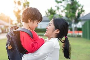 Mom hug and carry her son. Preparing to send her children back to school in morning. Mother playing with kids. Education and Back to school concept. Happy family and Loving of people theme photo