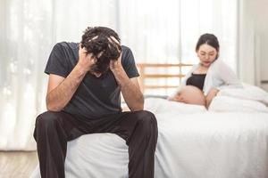 Worried stress man sitting on bed with hand on forehead in bedroom in serious mood emotion with pregnant wife woman background. Major Depressive Disorder called MDD concept. Physical healthcare photo