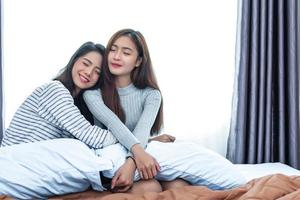 Two Asian Lesbian women hug together in bedroom. Couple people and Beauty concept. Happy lifestyle and home sweet home theme. Cushion pillow element and window curtain background. Love scene of lovers photo