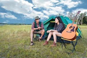 Two people talking near camping tent in meadow field. Male and female traveler looking at attraction view point. Couples adventure at outdoors together. People and lifestyles concept photo