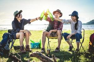 Group of young Asian friends enjoy picnic and party at lake with camping backpack and chair. Young people toasting and cheering bottles of beer. People and lifestyles concept. Outdoor background theme photo