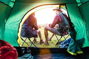 Male and female campers talking each others in front of camping tent. People and lifestyles concept. Picnic and travel concept. Nature in summer theme. Back view and inside of tent angle photo