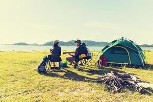 Group of travelers camping and doing picnic and playing music together. Mountain and lake background. People and lifestyle. Outdoors activity and leisure theme. Backpacker and Hiker. Back view angle photo