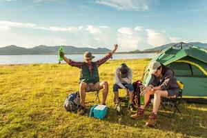 Drunken tourists doing party while camping and picnic in meadow field. Mountain and lake background. People and lifestyles concept. Outdoors activity and leisure theme. Backpacker and Hiker theme photo