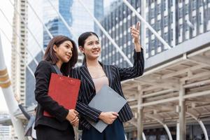 Two young businesswomen looking and pointing forward for thinking of future plan and sale break even point after marketing. Business teamwork employees of lifestyle working women. Boss and secretary photo