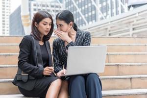 las mujeres de negocios chismean mientras usan la computadora portátil en el exterior. concepto de negocio y compañero de trabajo foto