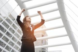 Happy business woman raise her hands at outdoors. Goal and successful concept. City and urban background photo
