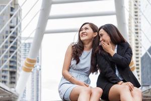 dos mujeres empresarias asiáticas chismes historia de broma en la ciudad al aire libre después de terminar de trabajar. Compañero de trabajo de las mujeres de negocios y concepto de la amistad. Hermosa gente de negocios hablando de un tema de escándalo secreto en la vida de la oficina foto