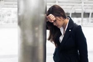 Mujer de negocios asiática cansada de exceso de trabajo y ataque al corazón al ir a casa después de trabajar horas extras. falta de sueño y concepto de salud. salud y estrés del empleado asalariado empresarial foto